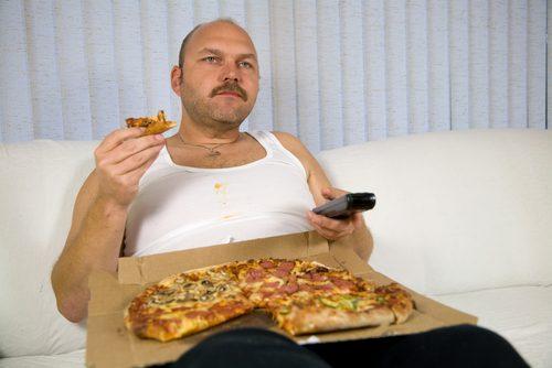 Señor en el sofá viendo la tele mientras se come una pizza