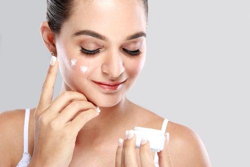 Mujer aplicándose una crema en el rostro.
