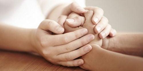 Manos abrazando las manos de otra persona