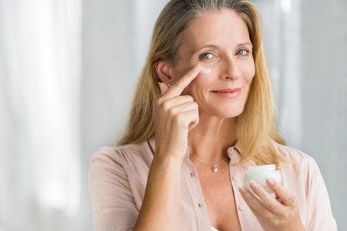 Mujer aplicándose crema sobre el rostro