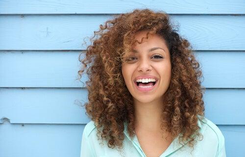 mujer feliz con pelo rizando sonriendo a la cámara