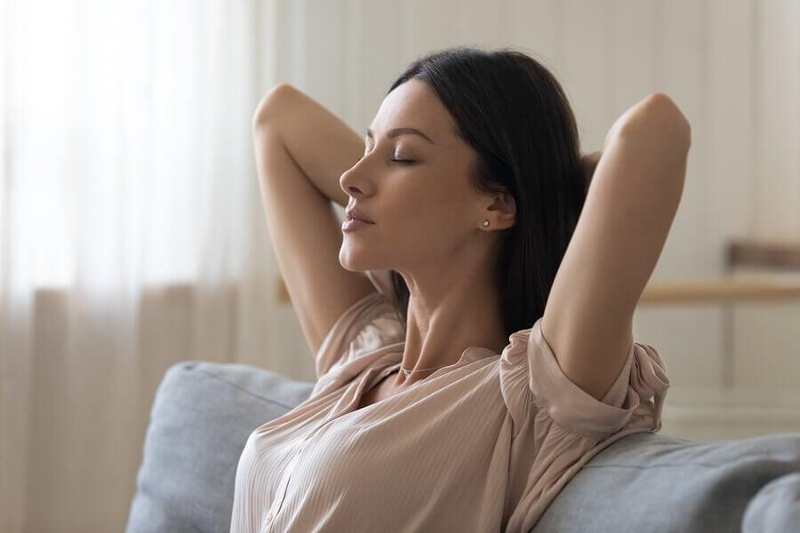 Mujer respirando hondo con los ojos cerrados.
