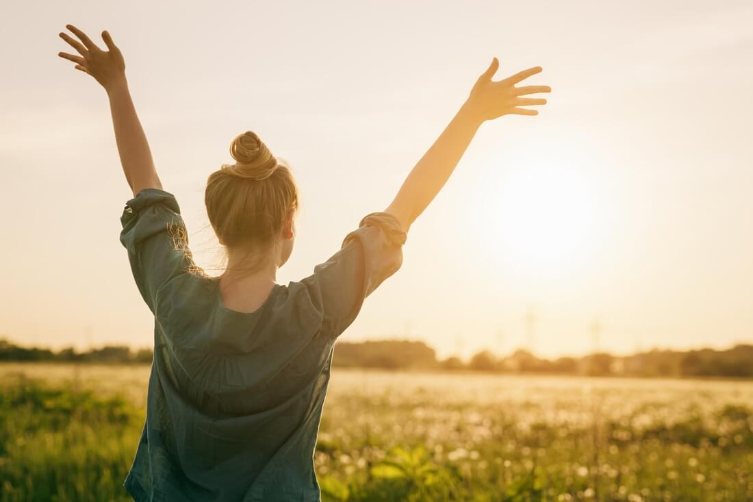 Mujer recibiendo el amanecer en su vida.