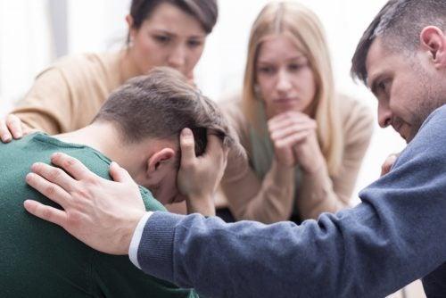 Chico llorando rodeado de amigos