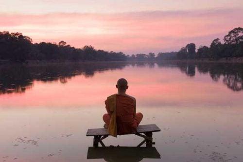 monje-meditando-delante-de-lago
