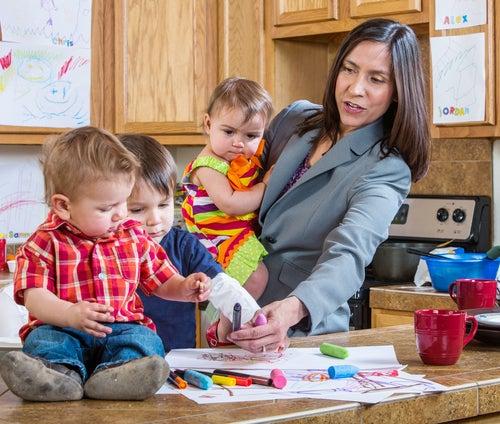 Mujer en la cocina con una niña en brazos y los otros dos hijos pintando en la cocina
