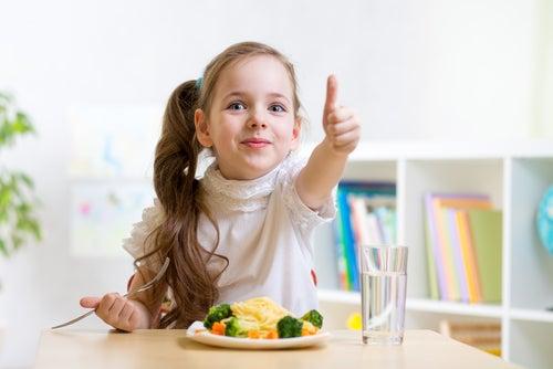 Niña con un plato y un vaso de agua levantando el dedo pulgar.