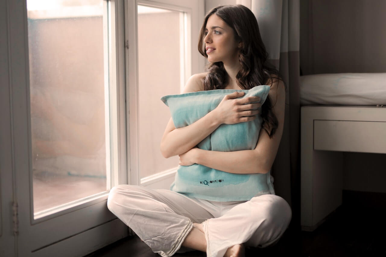 Mujer abrazando una almohada mirando por la ventana.