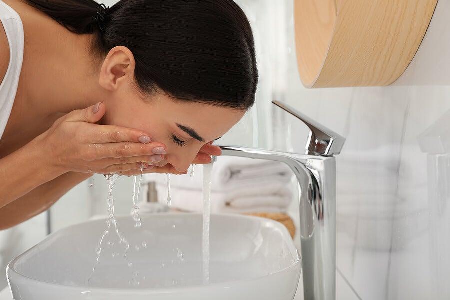 Mujer lavándose el rostro en el lavabo.