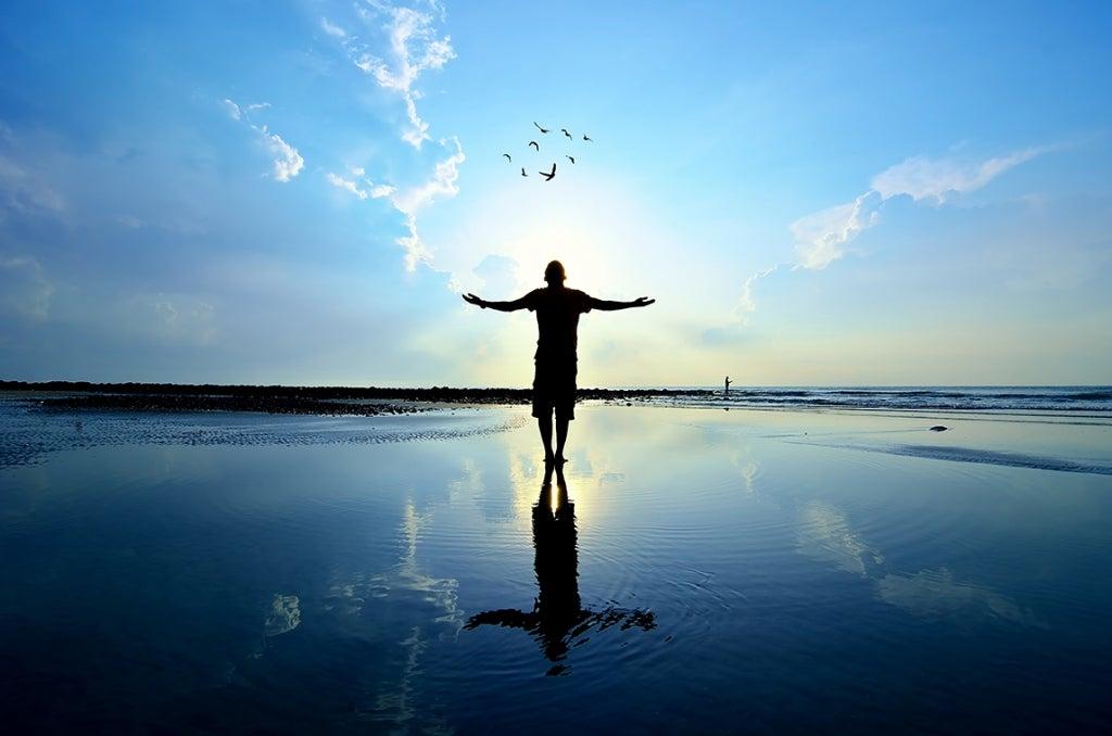 Hombre ene l mar con los brazos abiertos