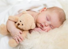 bebe-dormido-en-su-cuna-abrazando-un-peluche