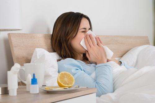 Mujer en la cama estornudando.
