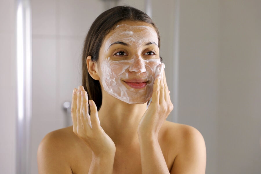 Mujer lavándose la cara para eliminar el acné.