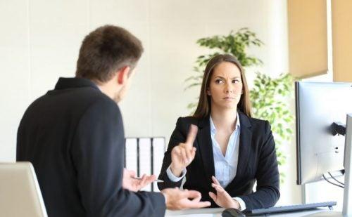 Mujer diciendo que no con el dedo a un hombre en el trabajo