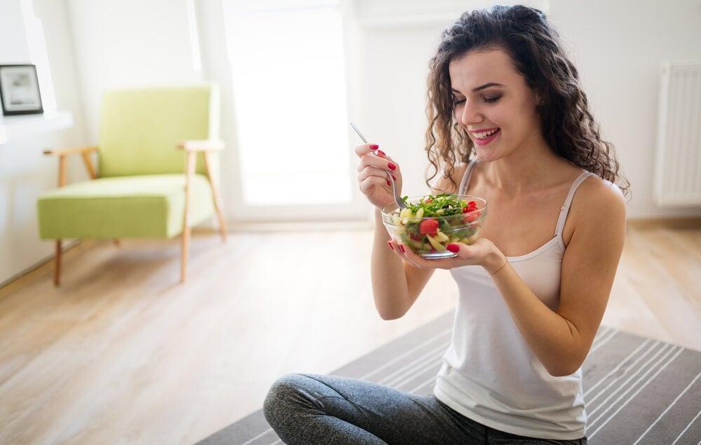 Mujer comiendo una ensalada.