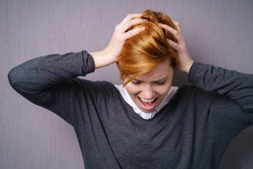 Mujer gritando con las manos en la cabeza