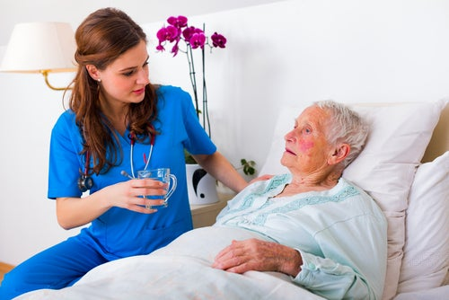 Mujer médico aplicando el tratamiento del Alzheimer a una paciente anciana