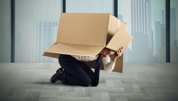 Hombre escondido debajo de una caja