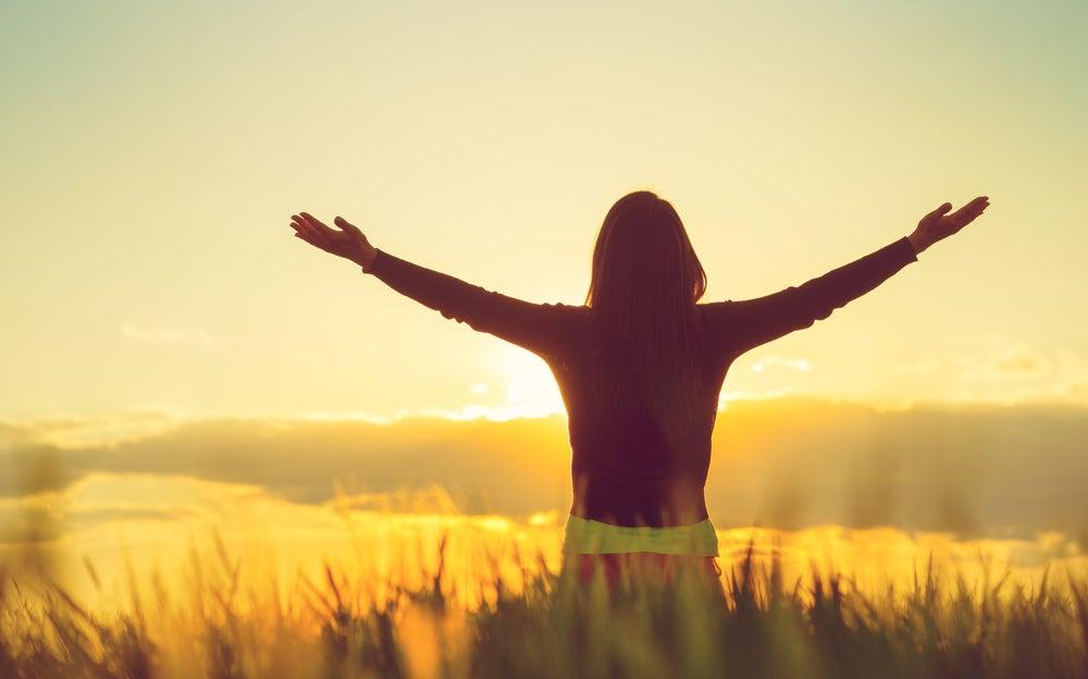 Mujer con los brazos abiertos trabajando la felicidad sostenible