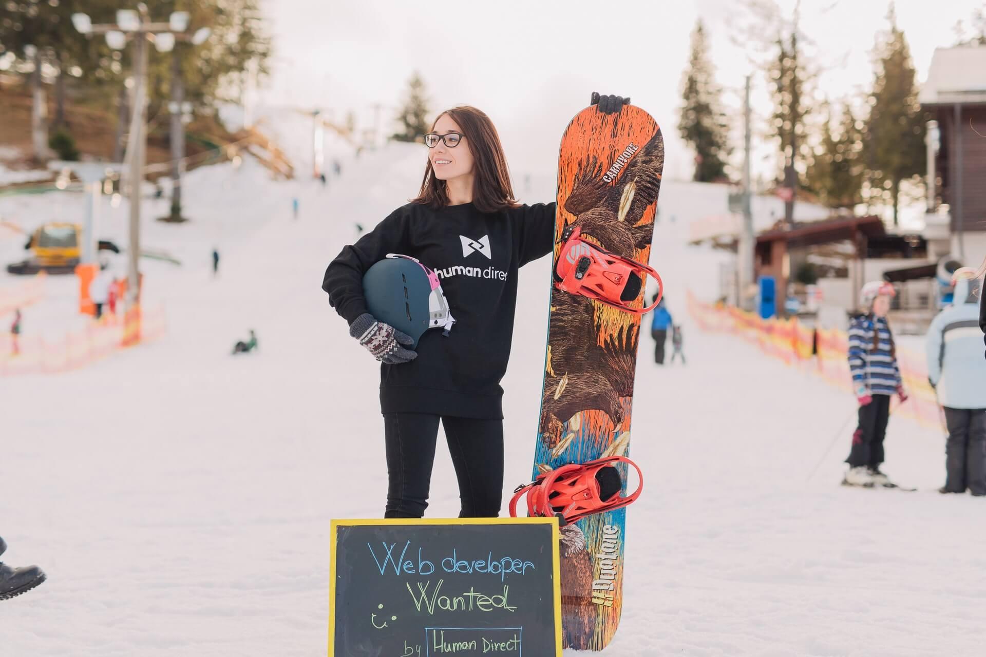 Mujer usando gafas y una tabla de snowboard.