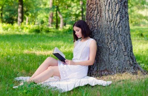 Mujer leyendo un libro bajo un árbol