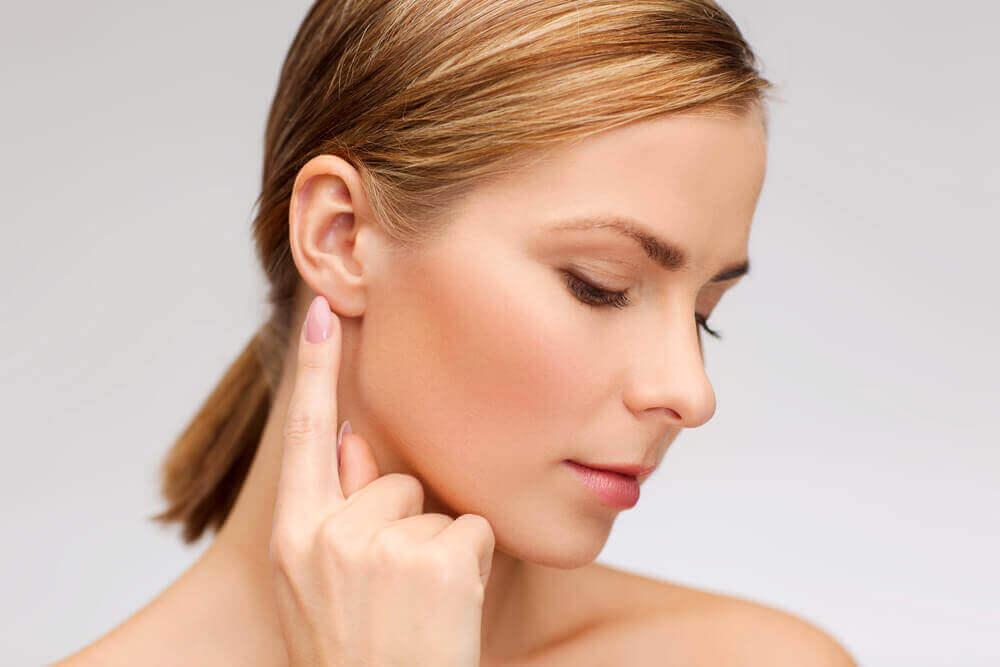 Mujer señalándose el oído.
