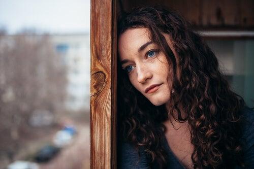 Mujer pensativa y triste mirando por la ventana,