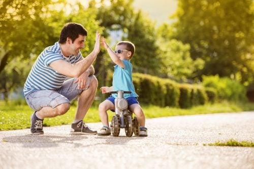 Padre chocando la mano con un niño en triciclo por el parque.