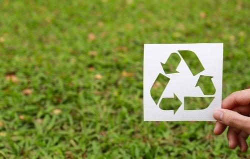 Logo de reciclaje sobre fondo de césped