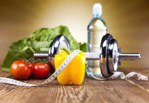 Alimentos saludables, una pesa y una cinta métrica