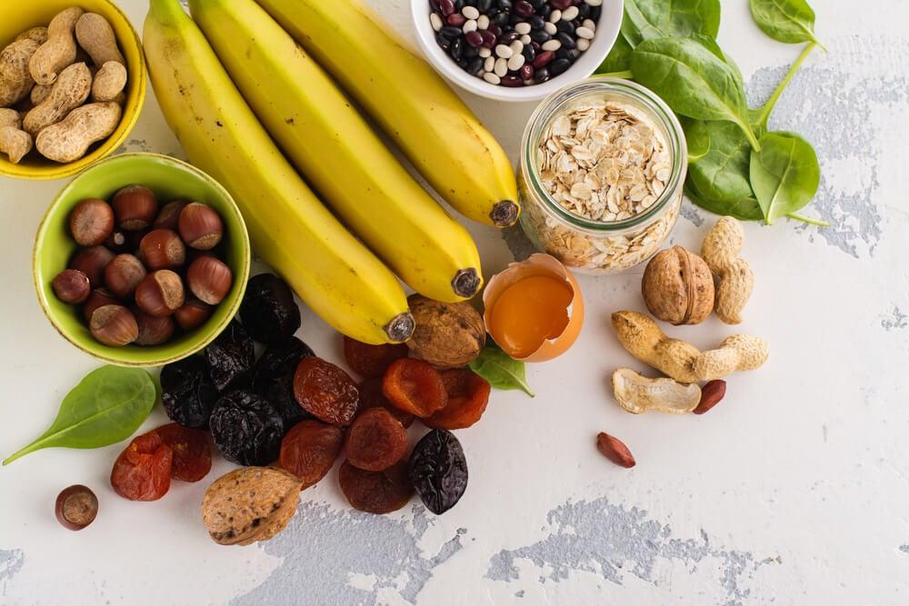 Conjunto de alimentos con potasio como frutos secos y plátanos.