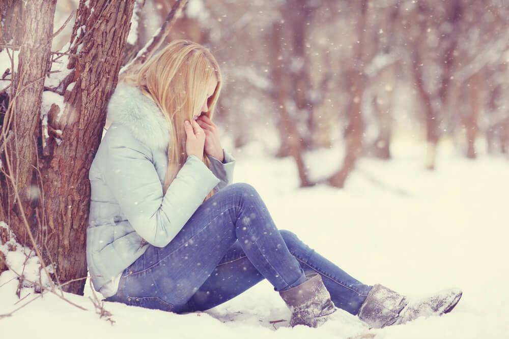 Mujer en la nieve con síntomas de hipotermia