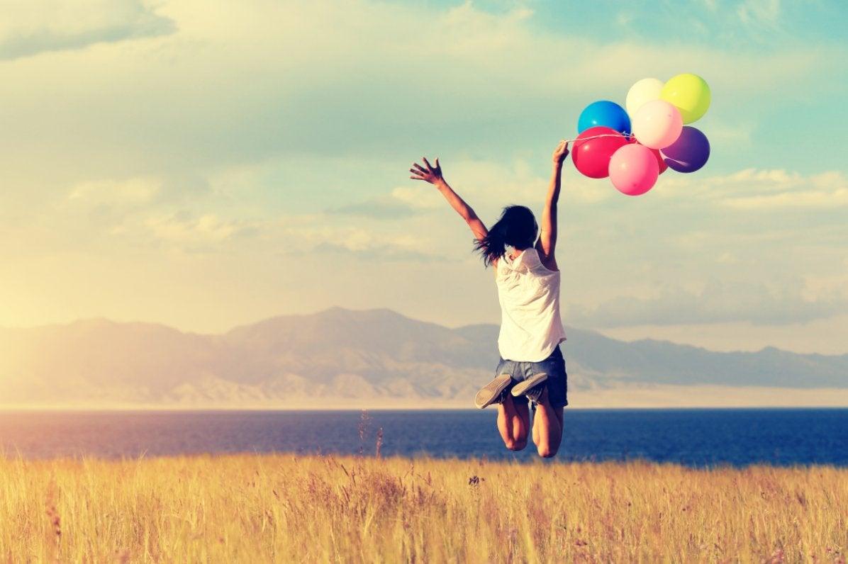 Mujer saltando con globos