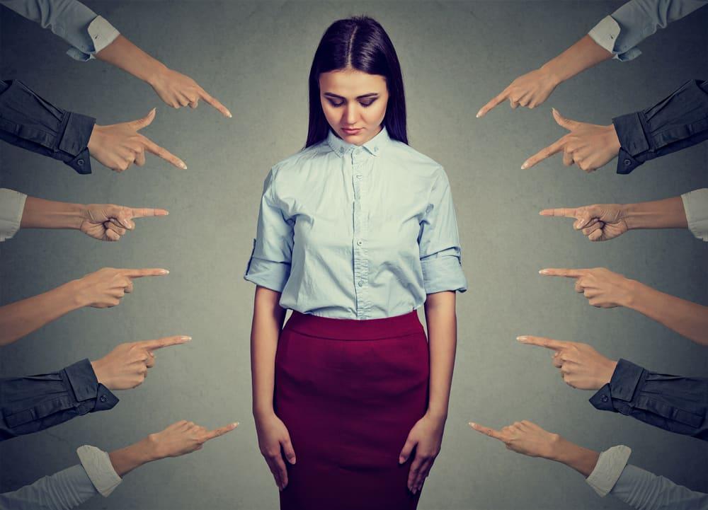 Mujer sintiéndose culpable la señalan varios dedos de manos apuntándola.