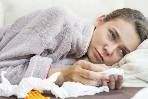 Mujer en la cama con resfriado