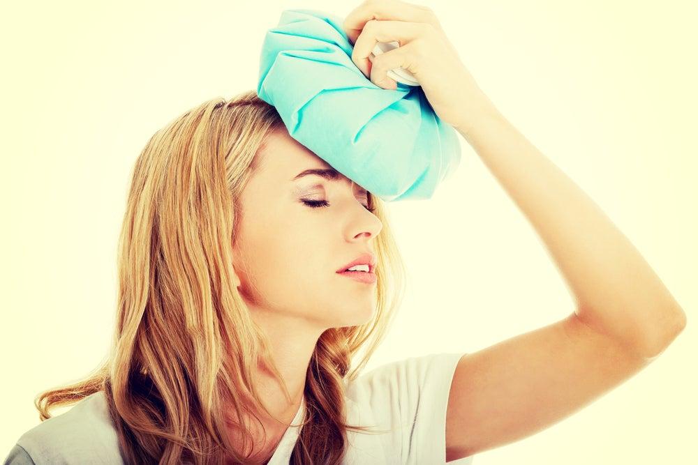 Mujer con dolor de cabeza como consecuencia de haber ingerido demasiado alcohol
