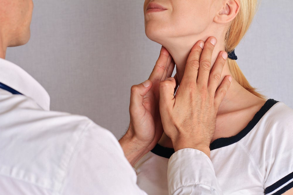Médico palpando la tiroides de una mujer