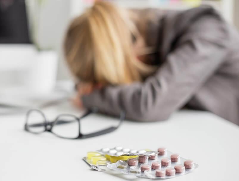 Mujer con la cabeza agachada y blisters de medicamentos. Migraña es un tipo de cefalea.