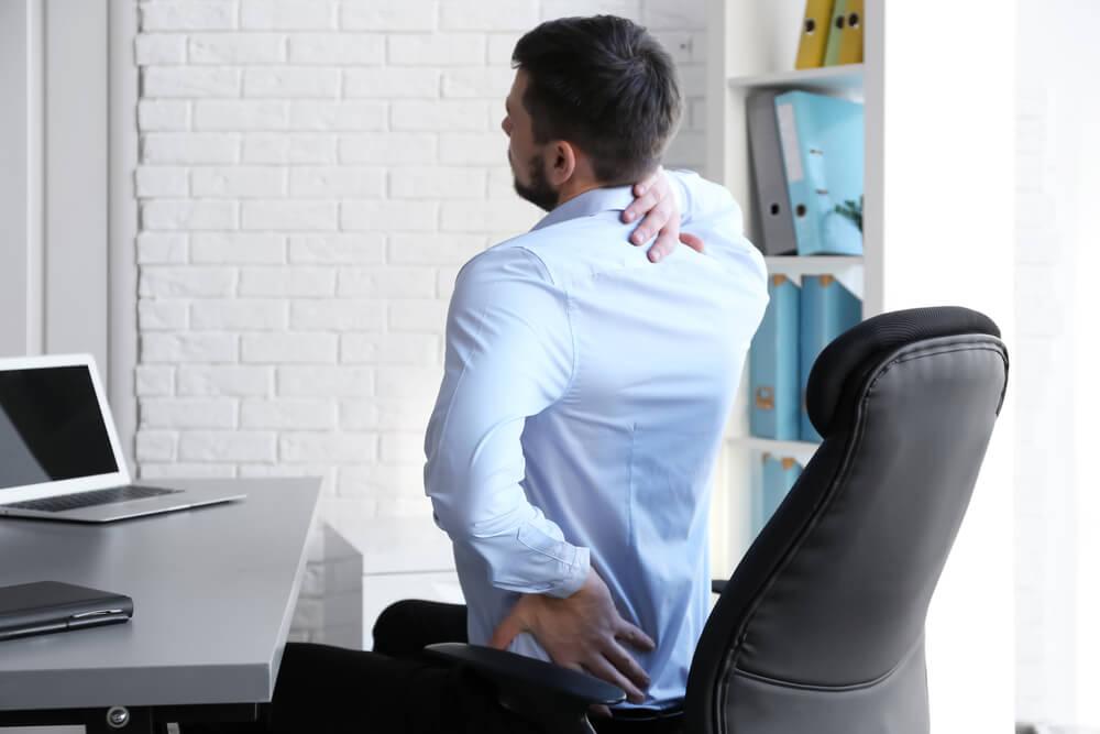 Hombre con dolor de espalda sentado en un despacho