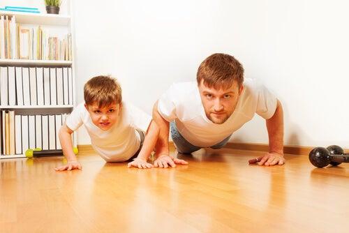 Padre practicando ejercicio con su hijo para promover el refuerzo positivo.