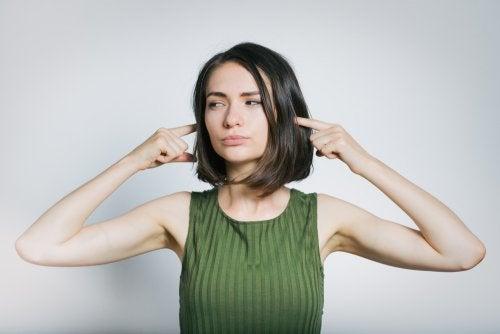 Mujer tapándose los oídos del ruido.