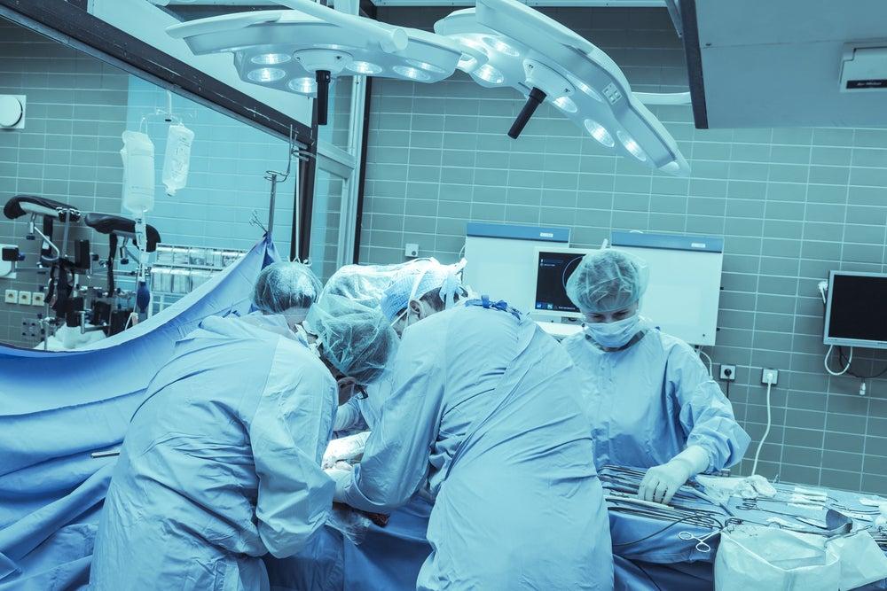 Cirujanos en el quirófano practicando una necrosectomía como tratamiento de la pancreatitis