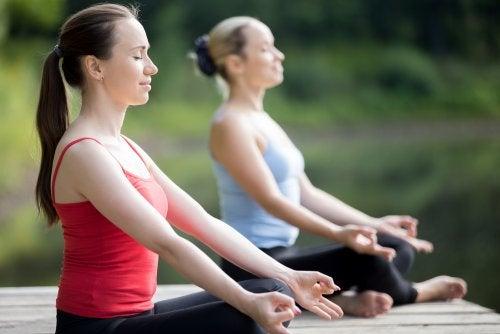 Dos mujeres hacen yoga al aire libre.