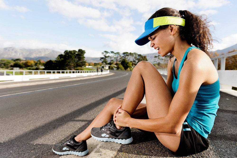 13883209 - runner with ankle injusry has sprained and strained ankle, painful expression. typical road running problem associated with shoe choice