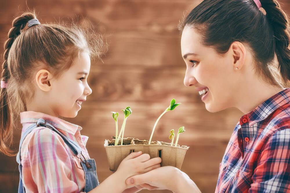Súper mamá con su hija sujetando macetas