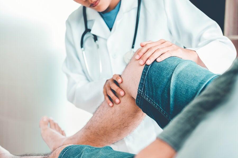 Médico examinando la rodilla de un paciente.