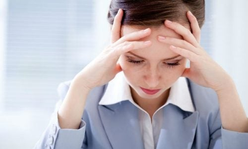 mujer con las manos en la cabeza que sufre preocupación crónica