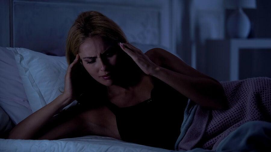 Mujer despertándose con dolor de cabeza nocturno.