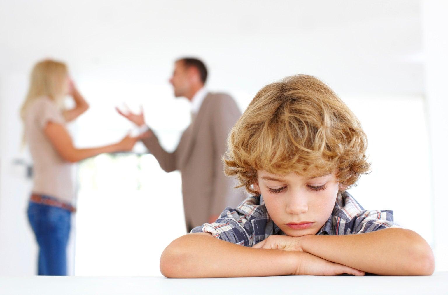 Niño triste con padres discutiendo al fondo.