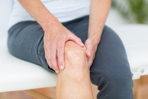 Hombre tocándose la rodilla: Osteoartritis de rodilla